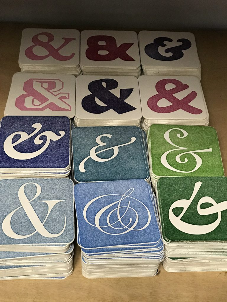 The 12 coaster designs are sitting on a shelf waiting for the ink to dry.