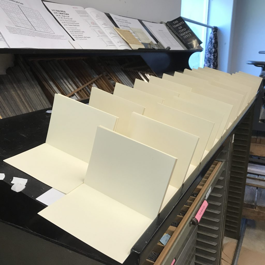 Rows of book signatures, folded to 90 degrees, laying on a table.